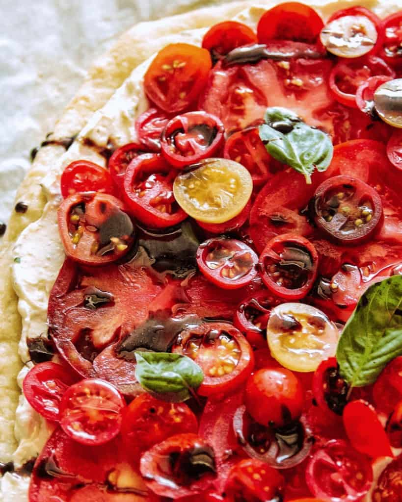 dozens of slices of tomatoes of varies colors and sizes with brown glaze drizzle and green herb leaves on a pizza crust with white spread
