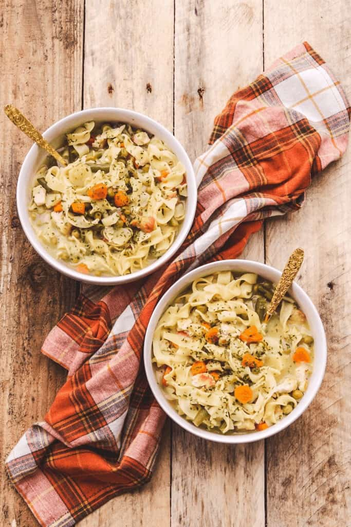 two bowls of chicken noodle soup on a wooden background with a fall colored linen napkin