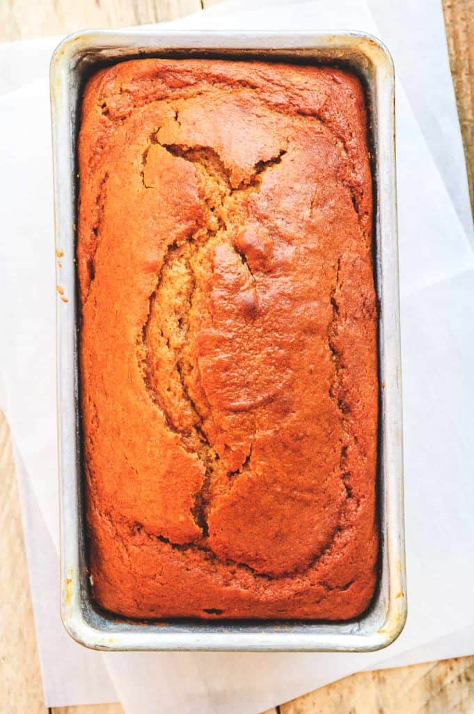 an orange brown loaf of pumpkin bread in a metal bread pan on parchment paper