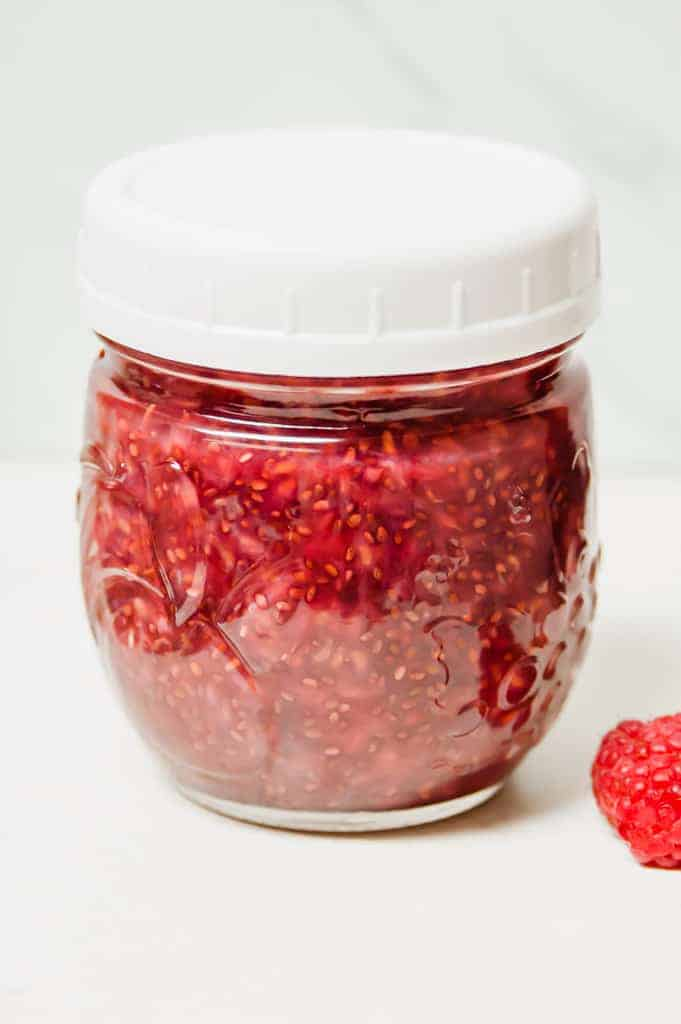 a round glass jar of red raspberry jam with a white lid