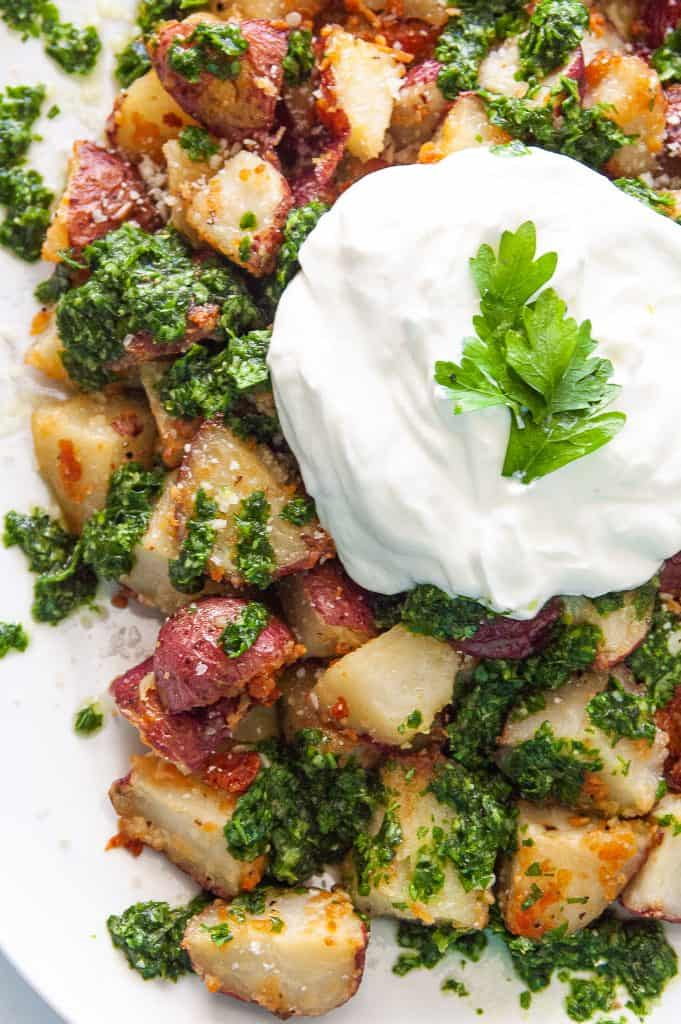 a big dollop of white cream over a plater of roasted red potatoes and green herb sauce