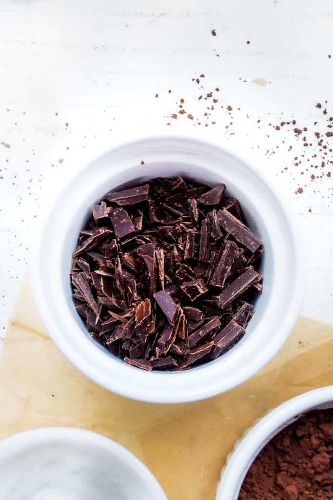 chopped bits of dark chocolate in a white bowl on a white background dusted with cocoa powder