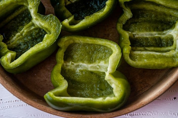 halves of raw green bell peppers with insides up in a round stone dish