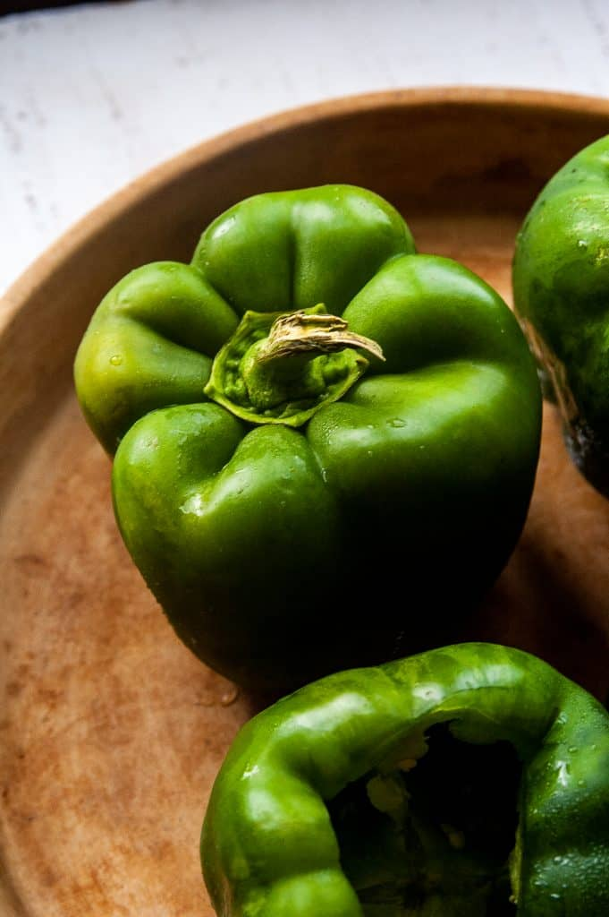 Whole raw green peppers in a brown colored round baking dish