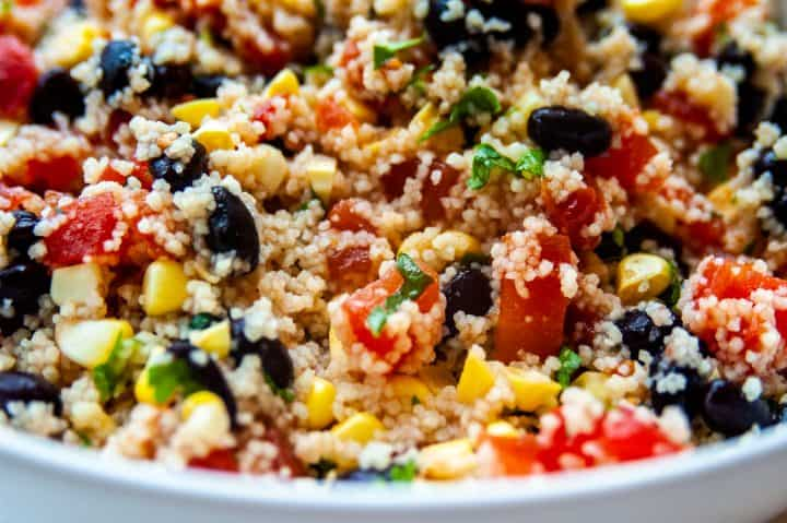 corn, diced tomatoes, couscous, black beans, and cilantro mixed together in a white bowl