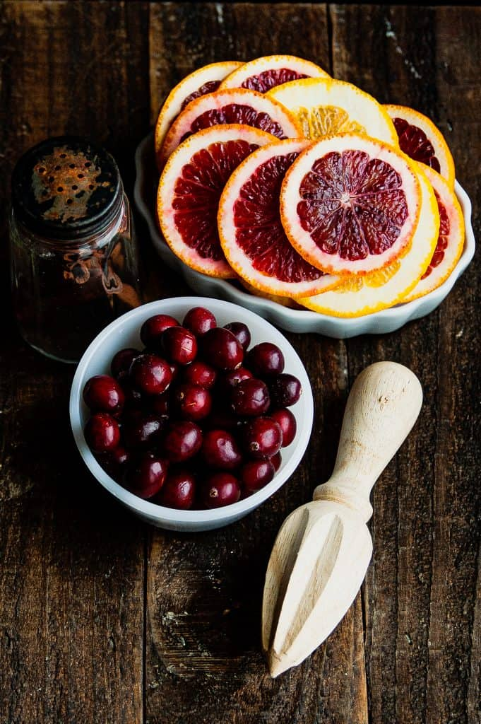 orange slices, a bowl of fresh cranberries, a jar of cinnamon sticks, and a wooden citrus juicer on a wooden board