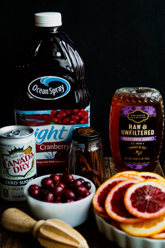 ingredients for a cranberry orange drink on a wooden board