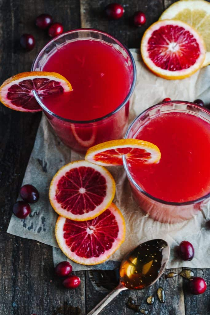 two glasses filled with pink juice and garnished with slices of oranges with red flesh