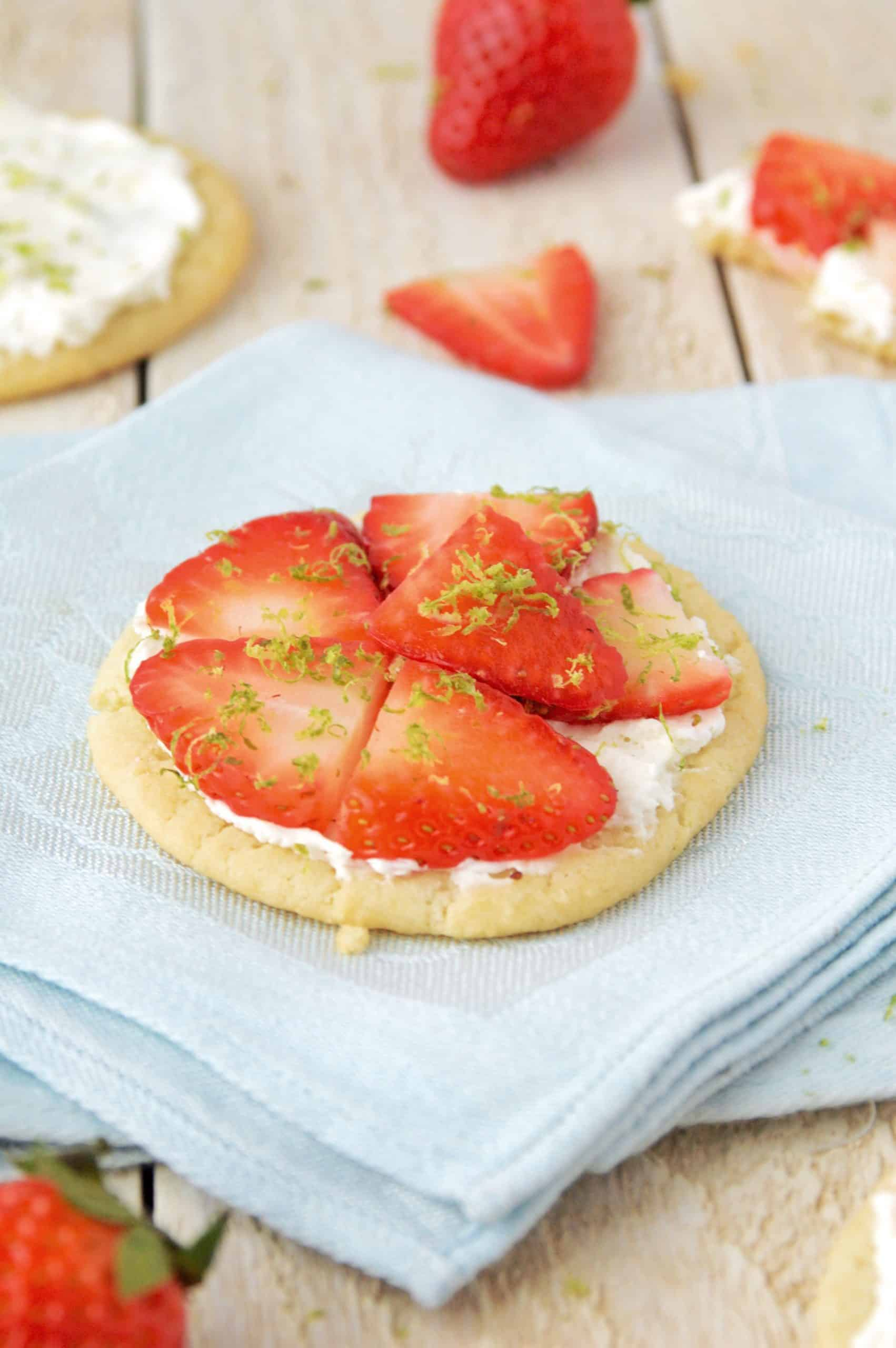a sugar cookie topped with white cream, slices of strawberries, and lime zest on a blue linen napkin over a whitewashed wooden surface
