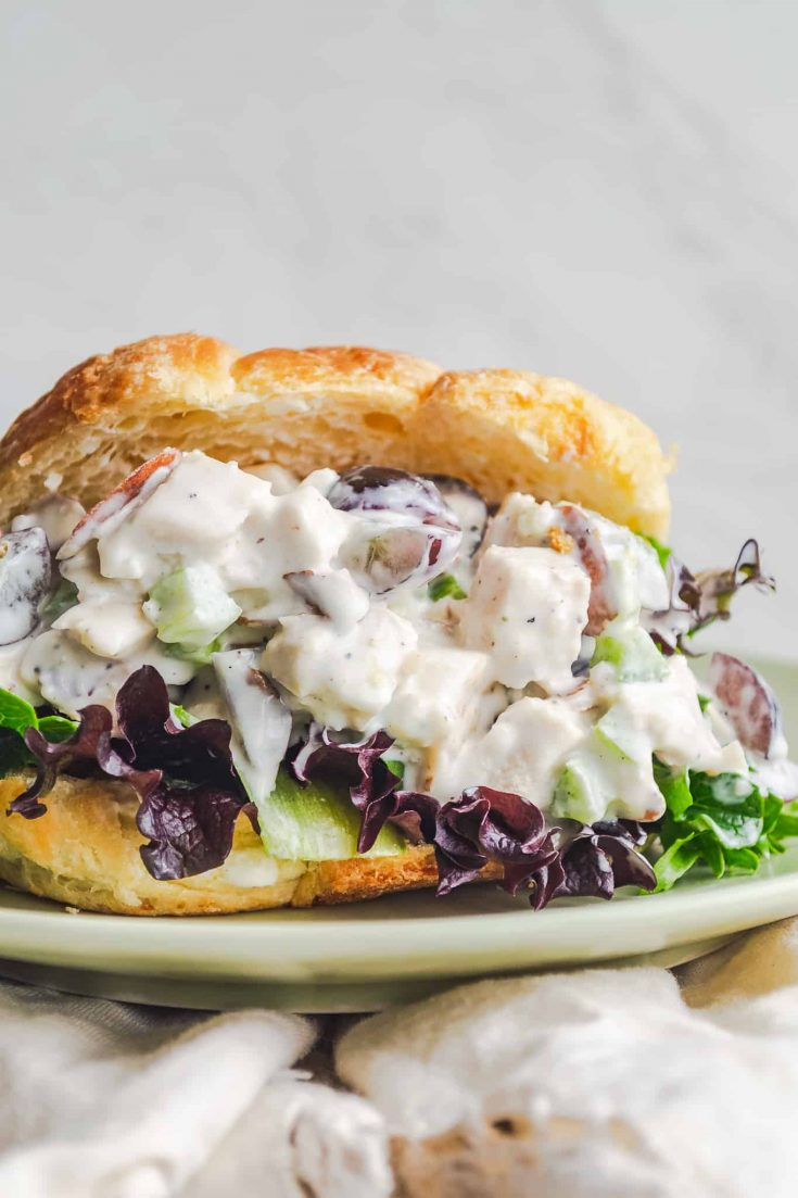golden croissant filled with chicken salad on a bed of purple and green lettuce