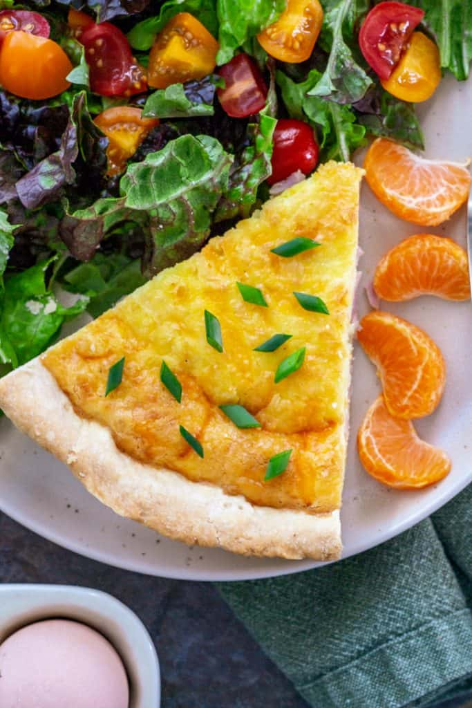 a slice of quiche garnished with chives on a plate a salad and orange slices